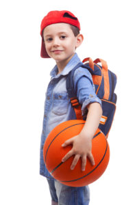 Portrait of a school kid holding a basketball, isolated on white background